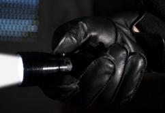 Einbrecher leuchtet mit Taschenlampe