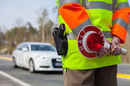 Polizist mit Kelle am Donnerstag (16.04.2015) an der B2 bei Heroldsberg. An einem Parkplatz an der B2 bei Heroldsberg war eine der vielen Messstellen der Polizei eingerichtet. Europaweit startete heute der Blitzmarathon. Foto: News5 / Grundmann