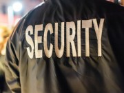 "The word ""security"" on the back of a security guard's jacket."