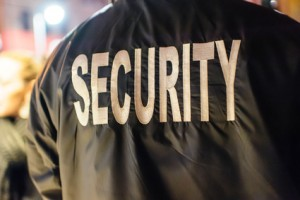 """The word """"security"""" on the back of a security guard's jacket."""