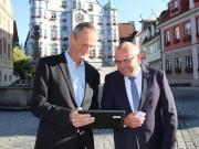 Pilotprojekt in Memmingen: Oberbürgermeister Manfred Schilder und Stefan Schachenmayr (links), Breitbandpate der Stadt, haben kostenfreies, offenes WLAN auf dem Memminger Marktplatz freigeschaltet.  Foto: Stadt Memmingen