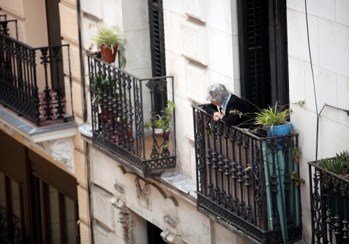 Seniorin schaut von einem Balkon, über dts Nachrichtenagentur
