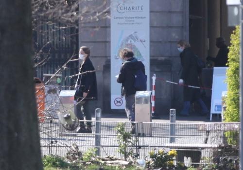 Menschen mit Schutzmaske vor einem Krankenhaus, über dts Nachrichtenagentur