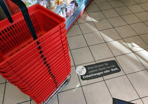 Einkaufskörbe mit Corona-Hinweis in Supermarkt, über dts Nachrichtenagentur