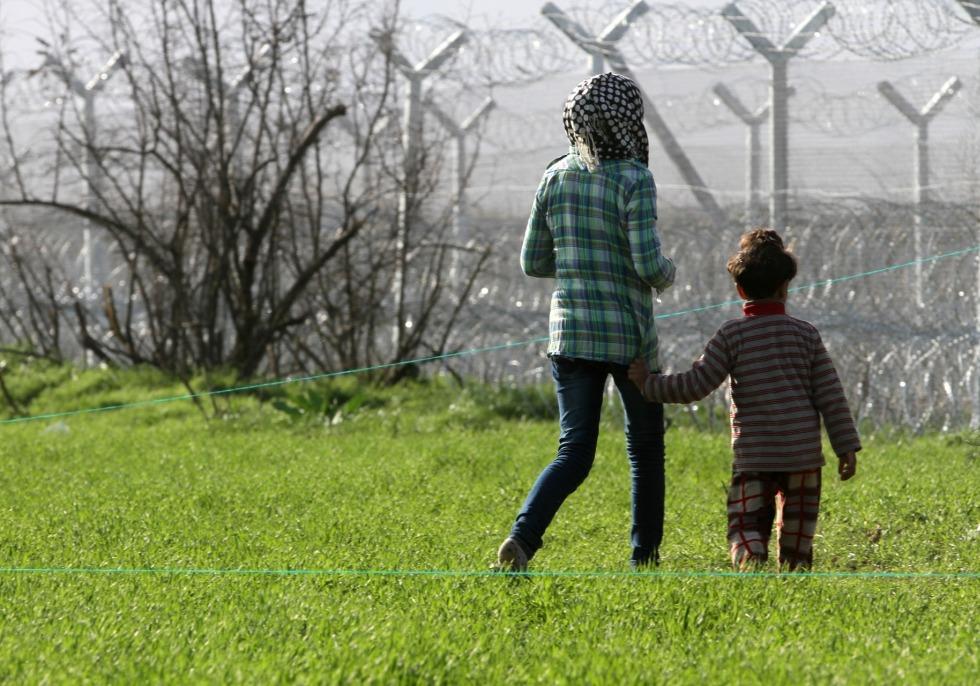Flüchtlinge vor einem Grenzzaun, über dts Nachrichtenagentur